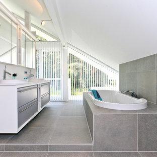 Mittelgroßes Modernes Duschbad mit flächenbündigen Schrankfronten, grauen Schränken, Einbaubadewanne, grauen Fliesen, Steinfliesen, weißer Wandfarbe, Einbauwaschbecken, grauem Boden und Zementfliesen in Sonstige