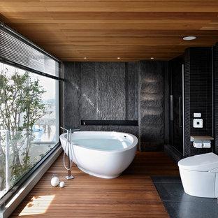 Immagine di una stanza da bagno etnica con vasca freestanding, pareti nere, pavimento in legno massello medio, doccia alcova, piastrelle a listelli e WC monopezzo