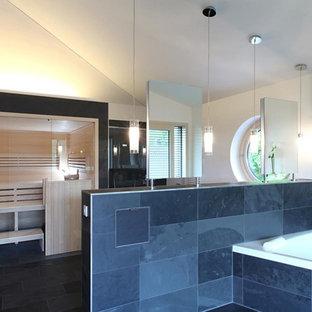 Ispirazione per un'ampia sauna minimal con vasca ad alcova, piastrelle nere, piastrelle in pietra, pareti bianche e pavimento in ardesia