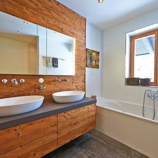 Mittelgroßes Rustikales Duschbad mit flächenbündigen Schrankfronten, hellbraunen Holzschränken, Einbaubadewanne, weißer Wandfarbe, Zementfliesen, Aufsatzwaschbecken und grauem Boden in München