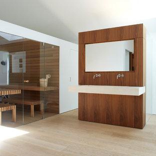 Modelo de sauna minimalista, extra grande, con paredes blancas, suelo de madera clara y lavabo de seno grande