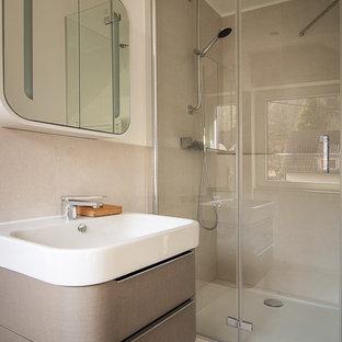 Modernes Duschbad mit flächenbündigen Schrankfronten, grauen Schränken, Duschnische, beigefarbenen Fliesen, weißer Wandfarbe, Waschtischkonsole, beigem Boden, Falttür-Duschabtrennung, Keramikfliesen, Keramikboden und Mineralwerkstoff-Waschtisch in Stuttgart