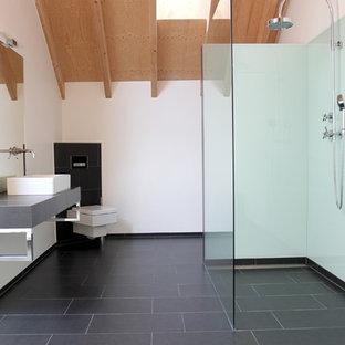 Mittelgroßes Modernes Duschbad mit Aufsatzwaschbecken, bodengleicher Dusche, Wandtoilette, weißer Wandfarbe, Fliesen aus Glasscheiben und Schieferboden in Stuttgart