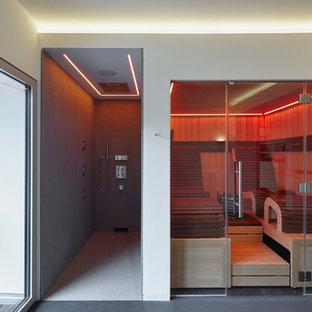 Imagen de sauna actual, de tamaño medio, con paredes blancas y suelo de cemento