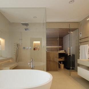 Großes Modernes Badezimmer mit flächenbündigen Schrankfronten, beigen Schränken, freistehender Badewanne, bodengleicher Dusche, beigefarbenen Fliesen, Zementfliesen, beiger Wandfarbe, Zementfliesen, Sauna, Aufsatzwaschbecken, Beton-Waschbecken/Waschtisch, beigem Boden und Falttür-Duschabtrennung in Sonstige