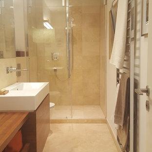 Ispirazione per una stanza da bagno con doccia minimal con ante lisce, ante in legno bruno, doccia alcova, WC sospeso, piastrelle beige, piastrelle in travertino, pareti beige, pavimento in travertino, lavabo sospeso, top in acciaio inossidabile, pavimento beige e porta doccia scorrevole