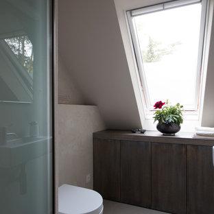 Ejemplo de cuarto de baño principal, actual, grande, con armarios con paneles lisos, puertas de armario de madera en tonos medios, bañera encastrada, ducha a ras de suelo, losas de piedra, paredes grises, lavabo integrado, encimera de mármol y suelo gris