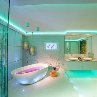 Immagine di un'ampia stanza da bagno padronale design con ante lisce, ante bianche, vasca freestanding, doccia a filo pavimento, WC sospeso, piastrelle beige, lastra di pietra, pareti bianche, pavimento in marmo, lavabo a bacinella e top in granito