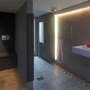 Großes Klassisches Duschbad mit flächenbündigen Schrankfronten, dunklen Holzschränken, bodengleicher Dusche, grauen Fliesen, Steinfliesen, grauer Wandfarbe und Waschtischkonsole in Köln