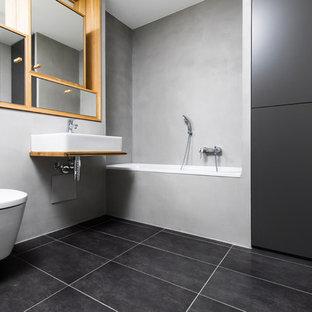 Idee per una stanza da bagno con doccia minimal di medie dimensioni con ante di vetro, vasca da incasso, WC sospeso, pareti grigie, pavimento in cementine, lavabo a bacinella, top in legno, pavimento nero e top marrone