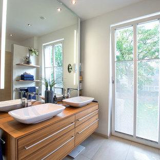 Mittelgroßes Modernes Badezimmer mit flächenbündigen Schrankfronten, hellbraunen Holzschränken, weißer Wandfarbe, Zementfliesen, Aufsatzwaschbecken, Waschtisch aus Holz, beigem Boden und brauner Waschtischplatte in Sonstige