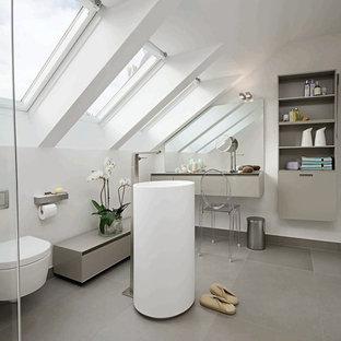 Cette image montre une salle de bain design de taille moyenne avec un lavabo de ferme, un placard sans porte, des portes de placard grises, un mur blanc, un sol en ardoise et un WC suspendu.