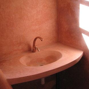 Immagine di una stanza da bagno mediterranea con pavimento in terracotta, lavabo integrato e pareti rosse