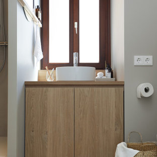 Small modern 3/4 bathroom in Frankfurt with flat-panel cabinets, light wood cabinets, an alcove shower, a two-piece toilet, gray tile, grey walls, cement tiles, a vessel sink, wood benchtops, multi-coloured floor, an open shower, a single vanity, a built-in vanity, wallpaper and wallpaper.