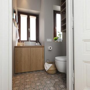 フランクフルトの小さいモダンスタイルのおしゃれなバスルーム (浴槽なし) (フラットパネル扉のキャビネット、淡色木目調キャビネット、アルコーブ型シャワー、分離型トイレ、グレーのタイル、グレーの壁、セメントタイルの床、ベッセル式洗面器、木製洗面台、マルチカラーの床、オープンシャワー、洗面台1つ、造り付け洗面台、クロスの天井、壁紙) の写真