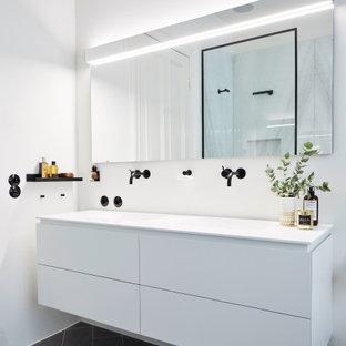 Modernes Badezimmer mit flächenbündigen Schrankfronten, weißen Schränken, weißer Wandfarbe, schwarzem Boden, weißer Waschtischplatte, schwebendem Waschtisch und Doppelwaschbecken in Hamburg