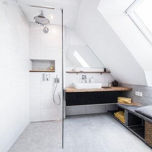 На фото: ванная комната среднего размера в современном стиле с настольной раковиной, серой плиткой, керамической плиткой, белыми стенами, полом из керамической плитки, душевой кабиной, черными фасадами, открытым душем, столешницей из дерева и открытым душем с