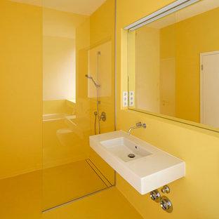 Ispirazione per una piccola stanza da bagno design con lavabo sospeso, doccia aperta, pareti gialle, WC sospeso e doccia aperta
