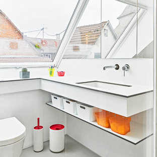 Doorless shower - small eclectic 3/4 concrete floor doorless shower idea in Stuttgart with flat-panel cabinets, white cabinets, a wall-mount toilet, white walls and an undermount sink