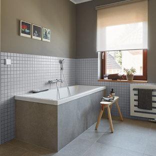 Diseño de cuarto de baño minimalista, de tamaño medio, con armarios con paneles lisos, bañera encastrada, sanitario de pared, baldosas y/o azulejos grises, baldosas y/o azulejos de cerámica, paredes grises, suelo de baldosas de cerámica, lavabo tipo consola y encimera de madera