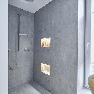 Immagine di una grande stanza da bagno padronale contemporanea con ante lisce, ante in legno scuro, doccia aperta, piastrelle bianche, piastrelle a specchio, pareti bianche, pavimento in cemento, lavabo a bacinella, top in vetro, pavimento grigio, doccia aperta e top grigio