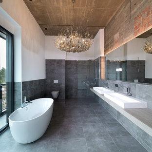 Großes Industrial Badezimmer En Suite mit freistehender Badewanne, bodengleicher Dusche, Steinfliesen, Keramikboden, Aufsatzwaschbecken, Mineralwerkstoff-Waschtisch, grauem Boden, offener Dusche, Wandtoilette, grauen Fliesen und weißer Wandfarbe in Sonstige