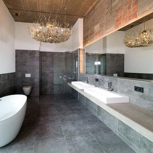 Modelo de cuarto de baño principal, urbano, grande, con bañera exenta, suelo de baldosas de cerámica, lavabo sobreencimera, ducha esquinera, sanitario de pared, paredes grises, suelo gris, ducha abierta, baldosas y/o azulejos grises, encimera de madera y encimeras grises