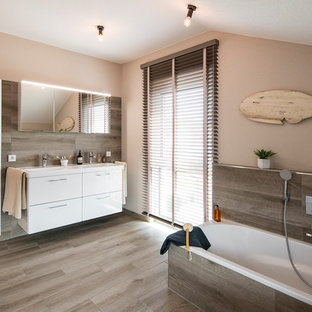 Mittelgroßes Modernes Duschbad mit weißen Schränken, Einbaubadewanne, bodengleicher Dusche, braunen Fliesen, braunem Boden, offener Dusche, weißer Waschtischplatte, flächenbündigen Schrankfronten, brauner Wandfarbe und Einbauwaschbecken in Sonstige