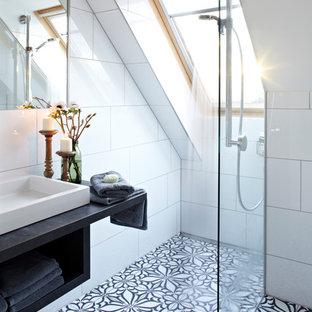 Immagine di una piccola stanza da bagno design con nessun'anta, piastrelle bianche, piastrelle in ceramica, pavimento con piastrelle in ceramica, lavabo a bacinella, doccia a filo pavimento, pareti bianche, top in legno e top nero