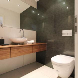 Großes Modernes Duschbad mit flächenbündigen Schrankfronten, hellbraunen Holzschränken, Wandtoilette, grauen Fliesen, Aufsatzwaschbecken, Waschtisch aus Holz, beigem Boden und brauner Waschtischplatte in Dortmund