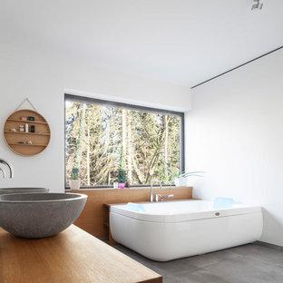 Foto på ett mellanstort funkis bastu, med ett fristående badkar, vita väggar, betonggolv, ett fristående handfat och grått golv