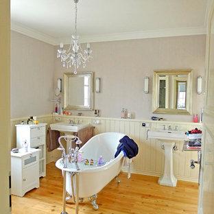 Immagine di una stanza da bagno country di medie dimensioni con vasca con piedi a zampa di leone, pareti beige, parquet chiaro e lavabo a colonna