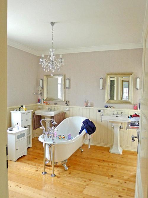 Mittelgroßes Country Badezimmer Mit Löwenfuß Badewanne, Beiger Wandfarbe,  Hellem Holzboden Und Sockelwaschbecken In