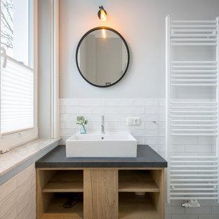 Kleines Modernes Badezimmer mit weißen Fliesen, grauer Wandfarbe, Aufsatzwaschbecken, offenen Schränken, Metrofliesen, hellen Holzschränken und grauer Waschtischplatte in Berlin