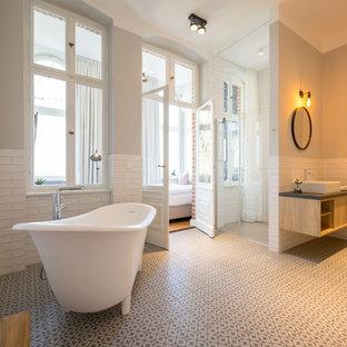 Großes Modernes Badezimmer En Suite mit offenen Schränken, freistehender Badewanne, weißen Fliesen, Metrofliesen, Keramikboden, Aufsatzwaschbecken, Falttür-Duschabtrennung, hellen Holzschränken, bodengleicher Dusche, grauer Wandfarbe, weißem Boden und grauer Waschtischplatte in Berlin