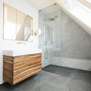 Großes Modernes Duschbad mit flächenbündigen Schrankfronten, hellbraunen Holzschränken, Duschnische, grauen Fliesen, weißer Wandfarbe, grauem Boden, offener Dusche, weißer Waschtischplatte, Duschbank, Einzelwaschbecken und eingebautem Waschtisch in Hamburg