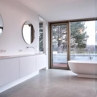 Geräumiges Modernes Badezimmer En Suite mit flächenbündigen Schrankfronten, weißen Schränken, freistehender Badewanne, bodengleicher Dusche, weißer Wandfarbe, Betonboden, integriertem Waschbecken, Mineralwerkstoff-Waschtisch, grauem Boden und offener Dusche in Bonn