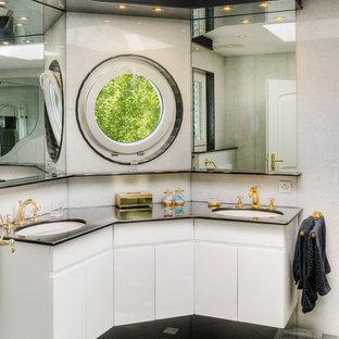 Klassisches Badezimmer mit flächenbündigen Schrankfronten, weißen Schränken, Keramikboden, Unterbauwaschbecken, schwarzem Boden und schwarzer Waschtischplatte in Sonstige