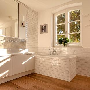 Idées déco pour une grand salle de bain contemporaine avec un placard à porte plane, des portes de placard blanches, une baignoire posée, un carrelage beige, un carrelage en pâte de verre, un mur blanc, un sol en bois peint, une vasque, un plan de toilette en surface solide et un plan de toilette blanc.