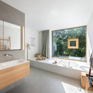 Geräumiges Modernes Badezimmer En Suite mit Einbaubadewanne, Betonboden, grauem Boden, weißer Waschtischplatte, hellen Holzschränken, grauen Fliesen, Porzellanfliesen, weißer Wandfarbe, integriertem Waschbecken und flächenbündigen Schrankfronten in München
