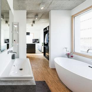 Immagine di un'ampia stanza da bagno padronale moderna con nessun'anta, ante nere, vasca freestanding, doccia a filo pavimento, WC a due pezzi, pareti bianche, parquet chiaro, lavabo a bacinella, top in superficie solida, doccia aperta e top bianco
