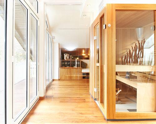 Großes Modernes Badezimmer Mit Flächenbündigen Schrankfronten, Hellbraunen  Holzschränken, Weißer Wandfarbe, Braunem Holzboden Und