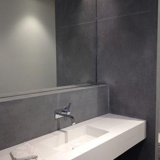 Foto di un'ampia stanza da bagno padronale design con ante di vetro, piastrelle nere, pareti nere, pavimento in cemento, lavabo a consolle, top in superficie solida, pavimento nero, top bianco, ante bianche e piastrelle in ardesia