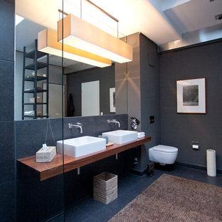 Modernes Badezimmer Mit Schwarzen Fliesen, Waschtisch Aus Holz,  Wandtoilette, Grauer Wandfarbe, Aufsatzwaschbecken
