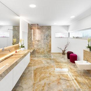 Großes Modernes Duschbad mit weißer Wandfarbe, Quarzit-Waschtisch, bodengleicher Dusche, Wandtoilette, flächenbündigen Schrankfronten, weißen Schränken, buntem Boden und integriertem Waschbecken in Sonstige