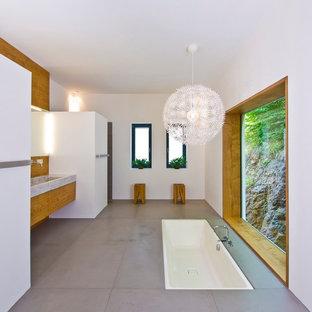 Ispirazione per una grande stanza da bagno padronale contemporanea con vasca sottopiano, pareti bianche, ante lisce, lavabo integrato e ante in legno scuro