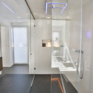 Design ideas for a large contemporary master bathroom in Frankfurt with flat-panel cabinets, dark wood cabinets, a freestanding tub, a curbless shower, a wall-mount toilet, beige tile, stone tile, beige walls, slate floors, an integrated sink, glass benchtops, black floor, an open shower, grey benchtops, an enclosed toilet, a double vanity, a floating vanity, wallpaper and wallpaper.