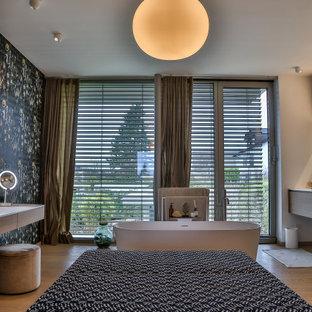Bild på ett stort funkis vit vitt en-suite badrum, med släta luckor, bruna skåp, ett fristående badkar, en kantlös dusch, en vägghängd toalettstol, grå kakel, cementkakel, beige väggar, mellanmörkt trägolv, ett integrerad handfat, bänkskiva i akrylsten, brunt golv och med dusch som är öppen