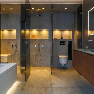 Esempio di una grande stanza da bagno padronale moderna con ante lisce, ante in legno bruno, vasca da incasso, doccia a filo pavimento, WC sospeso, piastrelle grigie, piastrelle in pietra, pareti grigie, pavimento in cementine, lavabo integrato, top in vetro, pavimento beige, doccia aperta, top verde, panca da doccia, due lavabi, mobile bagno sospeso, soffitto ribassato e boiserie