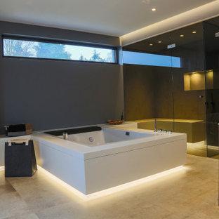 Modern inredning av ett stort grön grönt en-suite badrum, med släta luckor, skåp i mörkt trä, ett platsbyggt badkar, en kantlös dusch, en vägghängd toalettstol, grå kakel, stenkakel, grå väggar, cementgolv, ett integrerad handfat, bänkskiva i glas, beiget golv och med dusch som är öppen